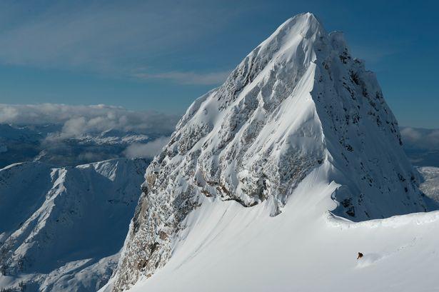 A skier passes below a precipitous snowy peak